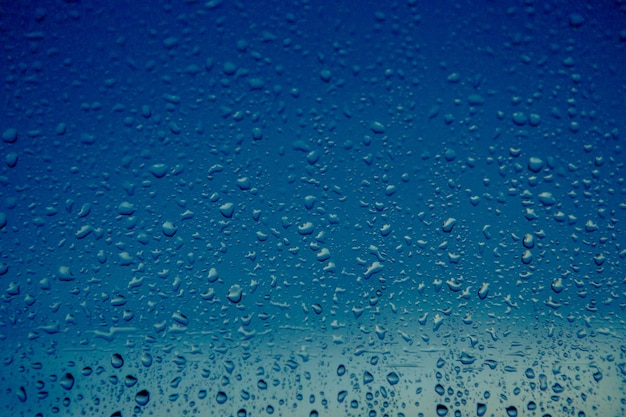 Gocce di pioggia scorrono dalla finestra di una casa