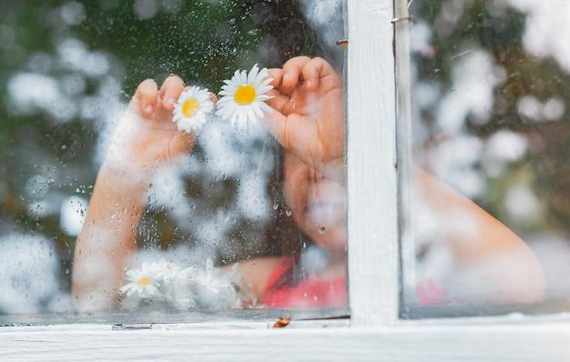Gocce di pioggia sul vetro di una finestra del villaggio, occhi di fiori di camomilla nelle mani dei bambini guardano la pioggia.