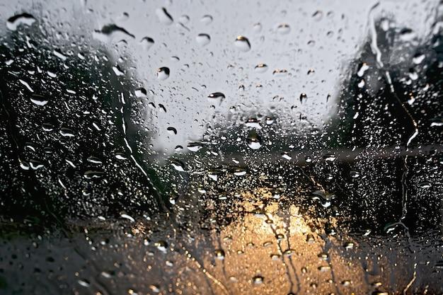 Gocce di pioggia sulla finestra di vetro con alberi sfocati, la strada e le luci gialle dell'auto