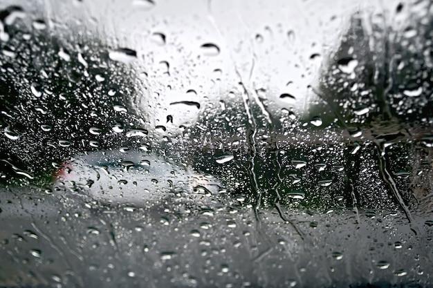 Gocce di pioggia su una finestra di vetro con alberi sfocati, strada e auto bianca