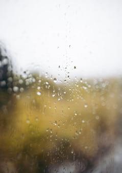 Gocce di pioggia su vetro con sfondo sfocato