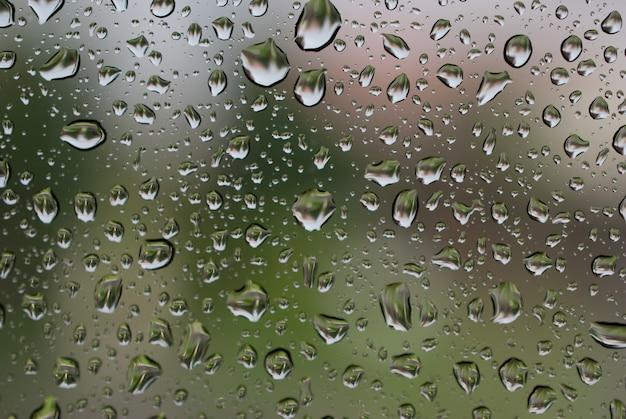 Gocce di pioggia su vetro con sfondo multicolore