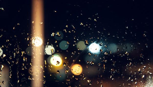 Gocce di pioggia sulla finestra sullo sfondo bokeh