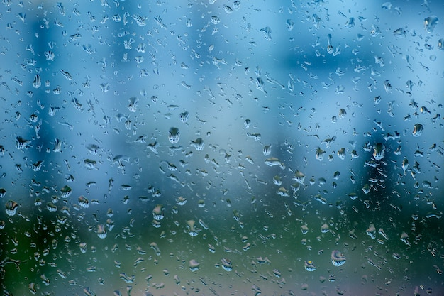 Gocce di pioggia su un vetro della finestra in una giornata piovosa