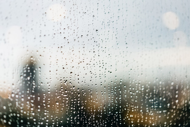 Gocce di pioggia sui vetri delle finestre nel crepuscolo con i semafori riflessi e sfocate grattacieli sullo sfondo.