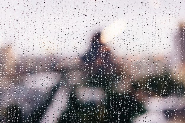 Gocce di pioggia sul vetro delle finestre nell'ora d'oro con sfocatura grattacieli sullo sfondo.