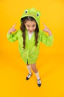 Gli accessori antipioggia rendono piacevole la giornata piovosa autunnale. accessorio impermeabile. kid ragazza felice indossare impermeabile. i bambini carini e impermeabili adorerebbero. stile rana. l'impermeabile con cappuccio da studentessa si gode il clima autunnale.