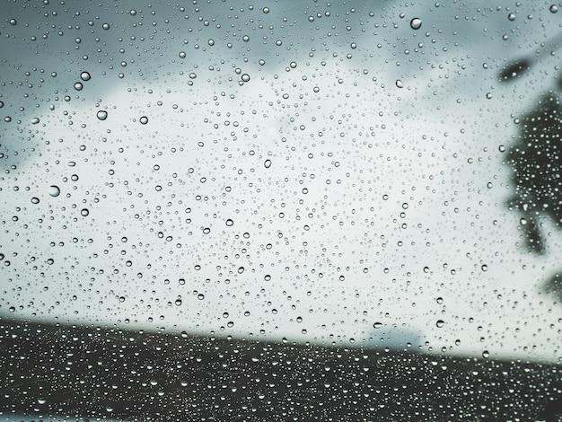 Piove gocce d'acqua sul finestrino dell'auto. concetto di sfondo e texture.