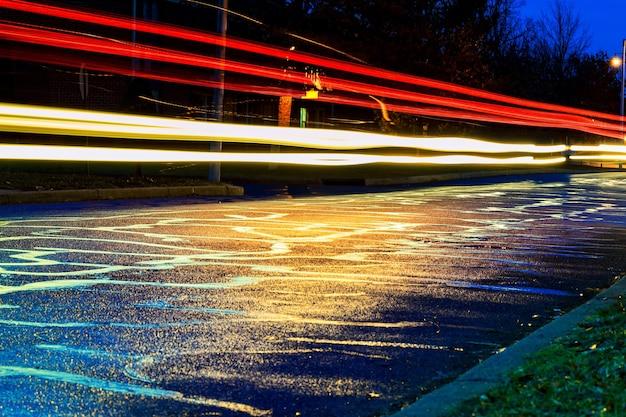 Temporale nella luce notturna della grande città dalle vetrine dei negozi riflessa sulla strada su cui transitano le auto...