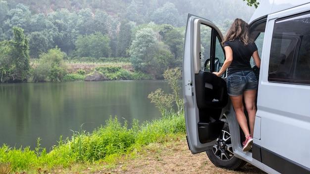Giornata di pioggia in estate bassa donna in un furgone in pantaloncini e schiena, non puoi vedere il suo viso