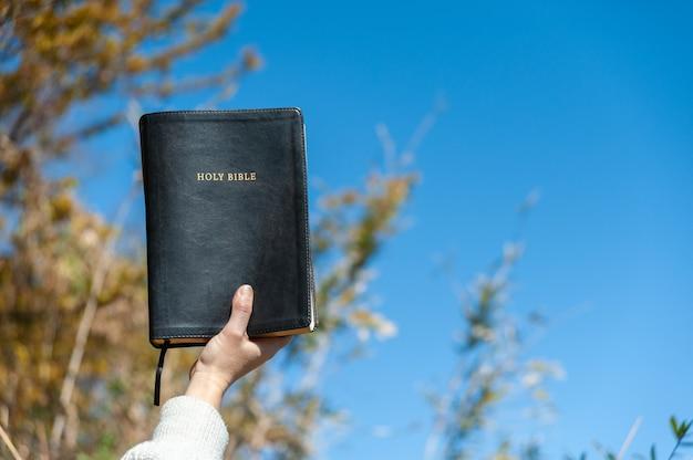Mano alzata che tiene la sacra bibbia