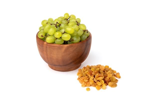 Uva passa e uva verde isolata su bianco