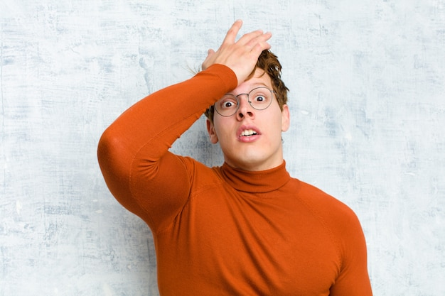 Alzando il palmo sulla fronte pensando oops, dopo aver fatto uno stupido errore o aver ricordato, sentendosi stupido