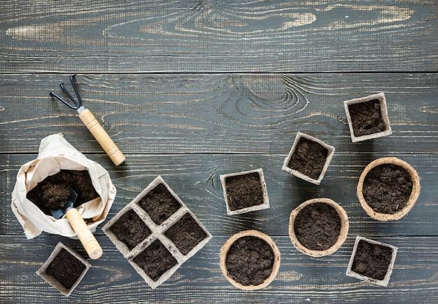 Rastrelli e vasi ecologici per piantine su fondo in legno, sacca con spatola da terra e giardino e rastrelli
