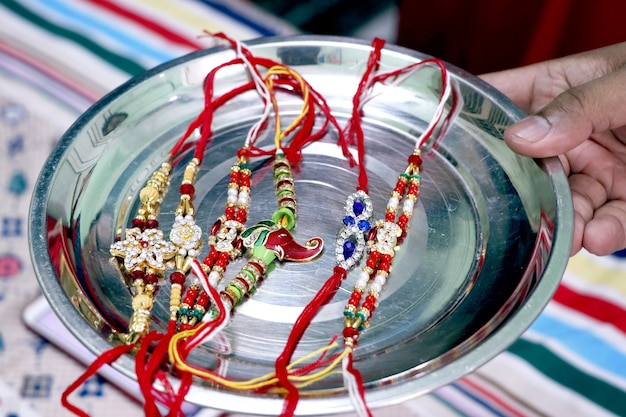 Raksha bandhan festival concetto mostra designer rakhi o fascia da polso con pooja thali, regali, dolci disposti su sfondo colorato. messa a fuoco selettiva