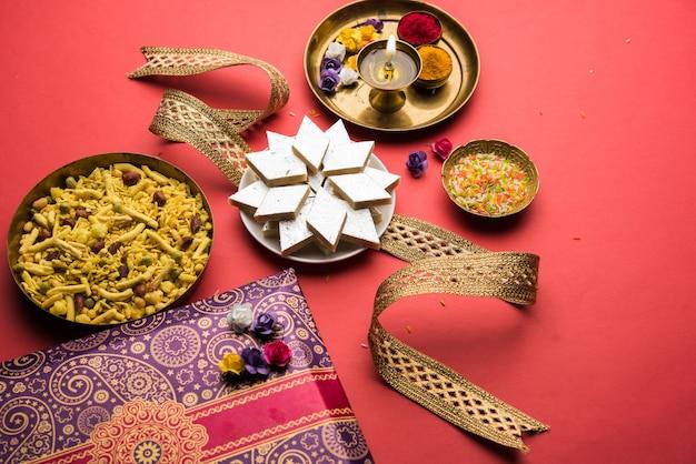 Raksha bandhan festival saluti: rakhi concettuale realizzato utilizzando un piatto pieno di kaju katli barfi o burfi e banda di fantasia e pooja thali. messa a fuoco selettiva