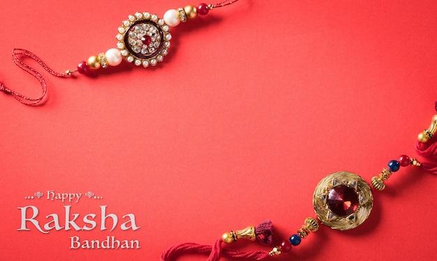 Raksha bandhan festival indiano con bellissimo rakhi su sfondo rosso