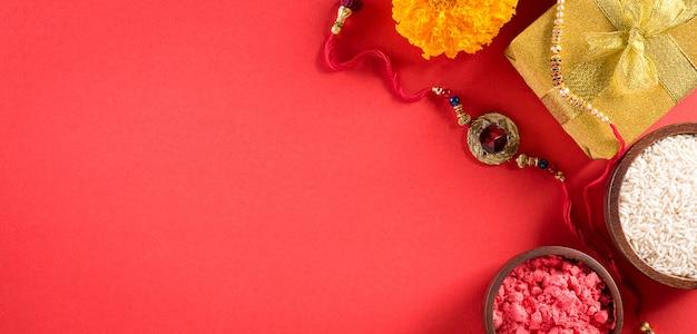 Raksha bandhan festival indiano con bellissimi rakhi e chicchi di riso su sfondo rosso