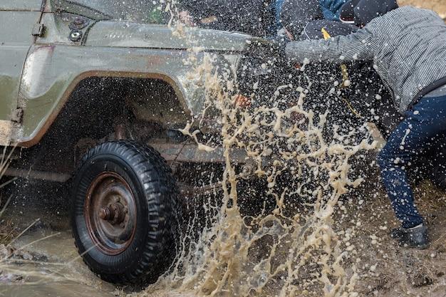 Rally su suv russi nel fango in inverno veicolo fuoristrada intrappolato tirato fuori dal fiume