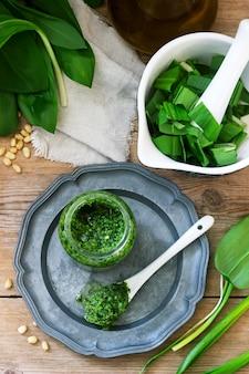 Pesto di aglio orsino e ingredienti per cucinarlo su una tavola di legno. stile rustico.