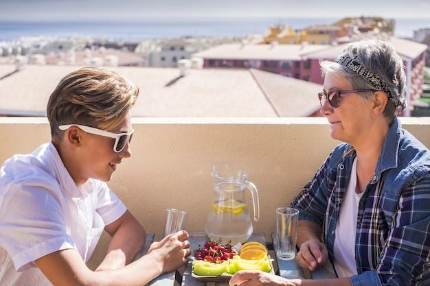Randmother e adolescente sulla terrazza facendo colazione.
