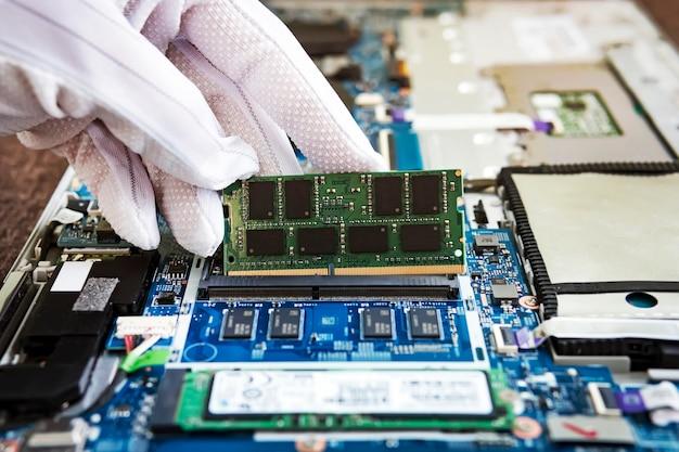 Memoria ad accesso casuale per la sostituzione al computer portatile. modulo ram ddr in mano sullo sfondo di un moderno trasformatore per notebook. aggiornamento dell'ultrabook. aumenta la quantità di ram nel computer.