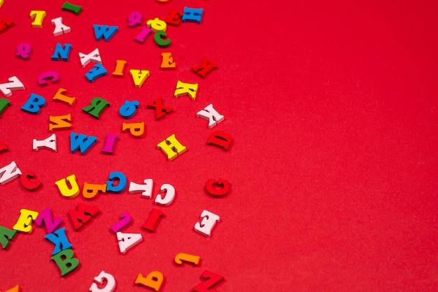 Alfabeto colorato casuale su sfondo rosso, lettere colorate. vista dall'alto.