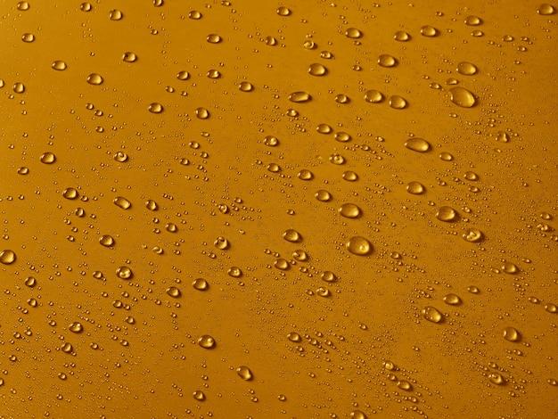 Gocce d'acqua casuali sulla superficie in pvc dorato