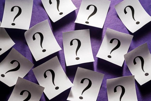 Punti interrogativi casualmente sparsi su carta bianca