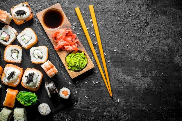 La gamma di diversi tipi di sushi, panini e maki con salse e bacchette. sulla tavola rustica nera