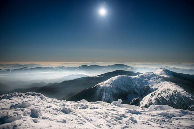 Gamma di montagne invernali nella neve bianca di notte sotto il cielo blu scuro con luna e stelle