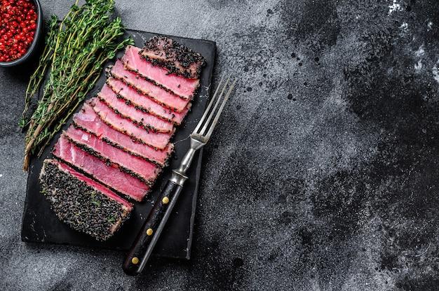 Rare fette di bistecca di tonno ahi con erbe fresche su un tagliere