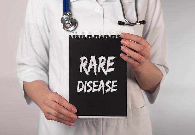 Testo di malattia rara su carta nelle mani del medico