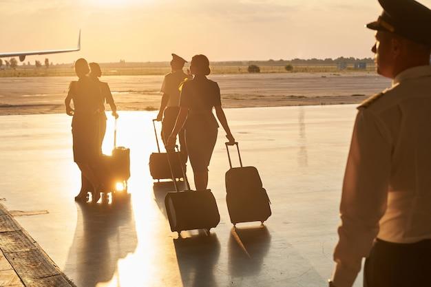 Vista rara dell'equipaggio della compagnia aerea di piloti e hostess che camminano con i bagagli all'aperto
