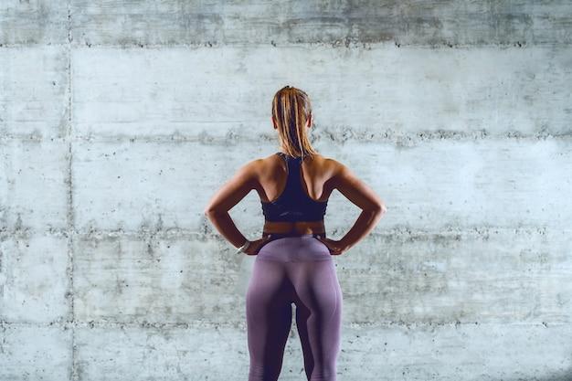 Vista rara di sportiva indoeuropea muscolare in forma in abiti sportivi con coda di cavallo in piedi con le mani sui fianchi.