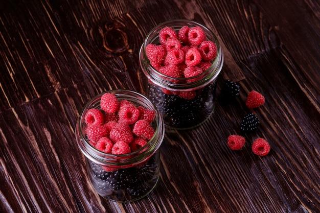 Bacche succose organiche dolci della mora e del lampone in due vasi di vetro sulla tavola di legno scuro