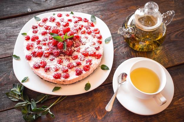 Cheesecake al lampone con tee verde sulla tavola di legno