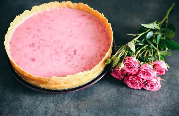 Cheesecake ai lamponi con fiori di rosa. regalo gustoso per le vacanze di san valentino o la festa della mamma. bellissimo appartamento adagiato sulla cucina. colori rosa sul dessert fatto a mano.