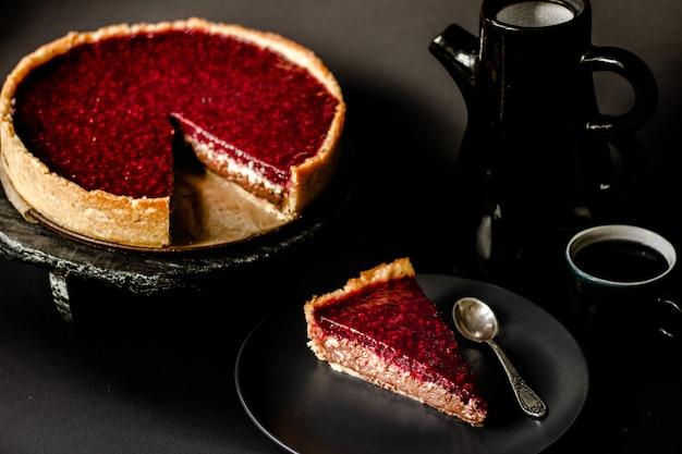 Crostata fatta in casa al cioccolato e cocco lampone con frutti di bosco su un'elegante superficie scura