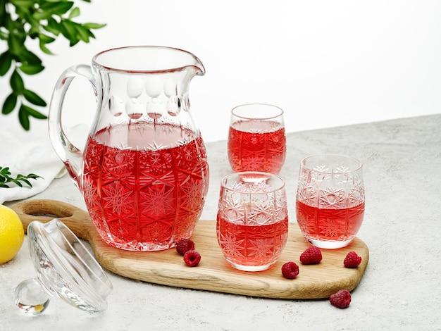 Bevanda al lampone in una brocca e tre bicchieri.