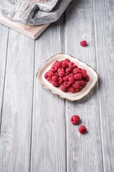 Frutti di lampone nel piatto vicino a vecchi taglieri