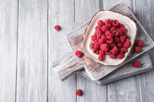 Frutti di lampone nella piastra sul vecchio tagliere, mucchio sano di bacche estive su fondo di legno grigio, spazio della copia di vista superiore per testo