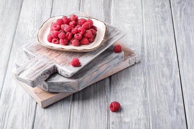 Frutti di lampone nella piastra su vecchi taglieri, mucchio sano di bacche estive sulla tavola di legno grigio, angolo di visione