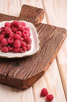 Frutti di lampone nel piatto sul vecchio tagliere in teak, mucchio sano di bacche estive su una superficie di legno, angolo di visione