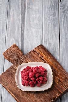 Frutti di lampone nella piastra sul vecchio tagliere in teak, mucchio sano di bacche estive sulla tavola di legno, angolo vista copia spazio per il testo