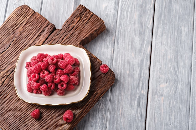 Frutti di lampone nel piatto sul vecchio tagliere in teak. vista yop