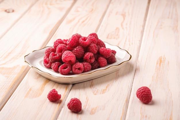 Frutti di lampone nel piatto bianco, mucchio sano di bacche estive su una superficie di legno, vista angolare