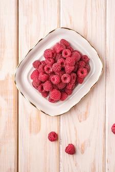 Frutti di lampone nel piatto bianco, mucchio sano di bacche estive su legno