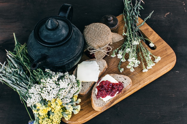 Marmellata di lamponi e pane con burro in un barattolo e tisana calda sul tavolo di legno pranzo colazione