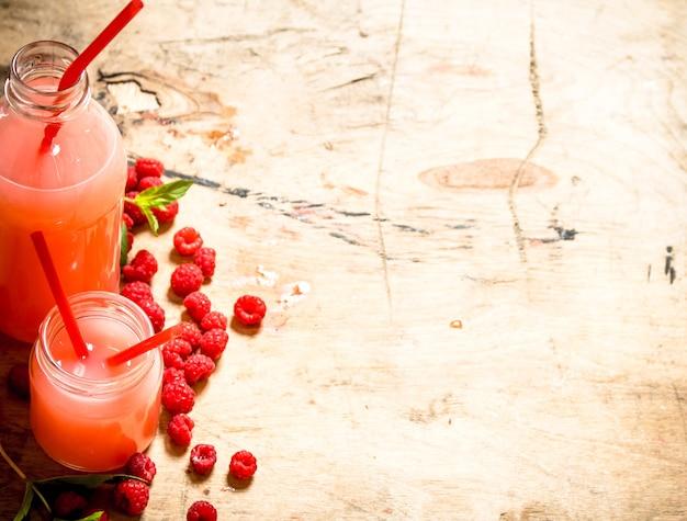 Succo di lampone nella brocca e nei bicchieri. su un tavolo di legno.